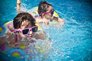 Two kids in swimming pool wearing sunglasses
