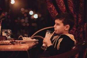 Boy drinking tall drink at restaurant